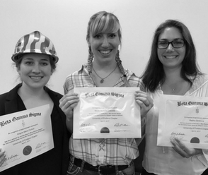 Three female students holding up their certificates for admittance into Beta Gamma Sigma