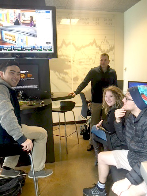 Three students and professor at Bloomberg Terminal