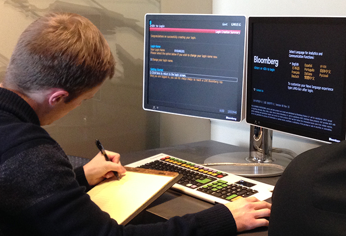 Student using Bloomberg terminals and making notes on his findings