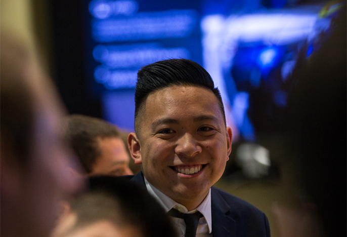 Male student in suit smiling at camera