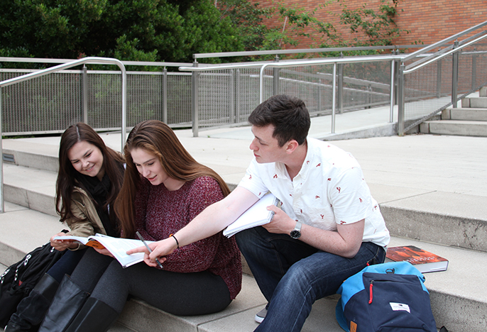 Three students studying outside on the steps of Clark Library