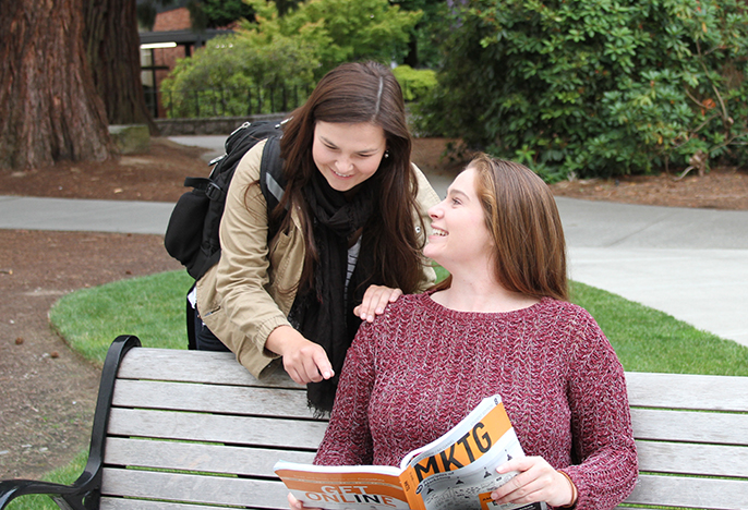 Two students discussing marketing outside on a bench.